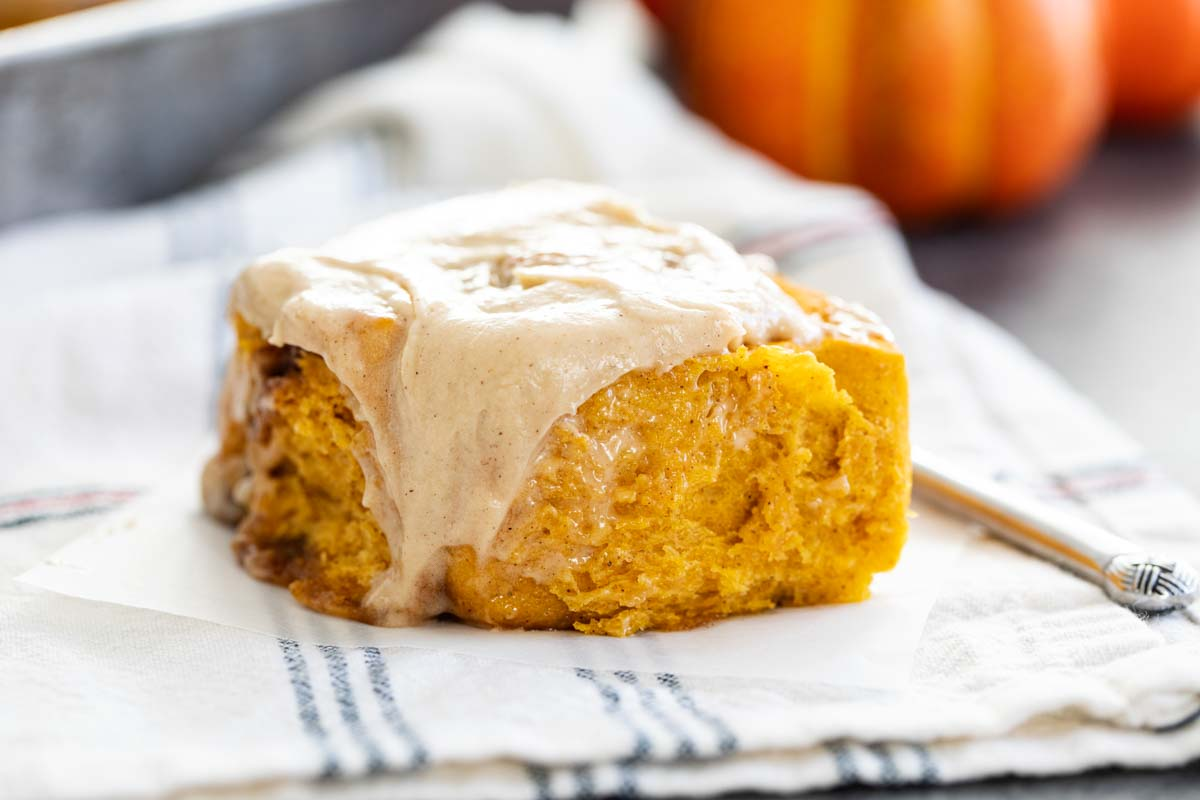 Pumpkin Cinnamon Roll with frosting dripping down the side