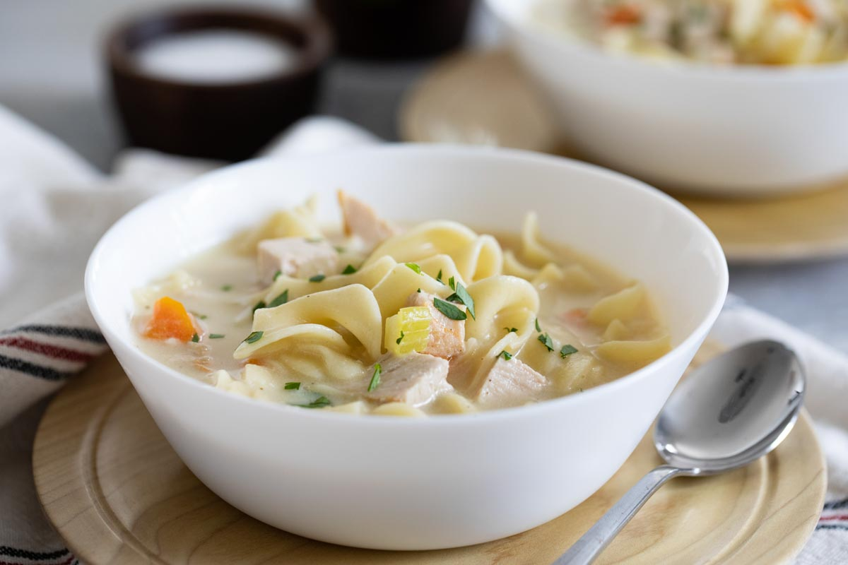 bowl of Creamy Turkey Noodle Soup with a spoon on the side