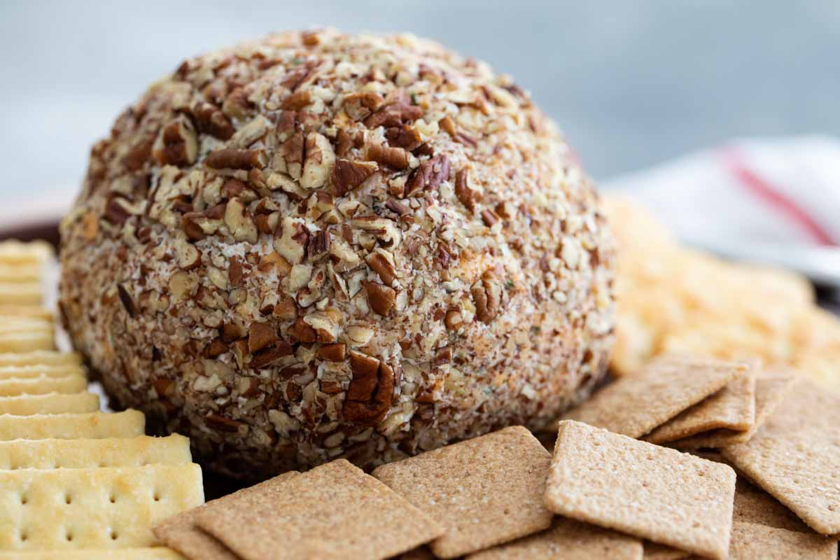 cheese ball coated in pecans surrounded by crackers
