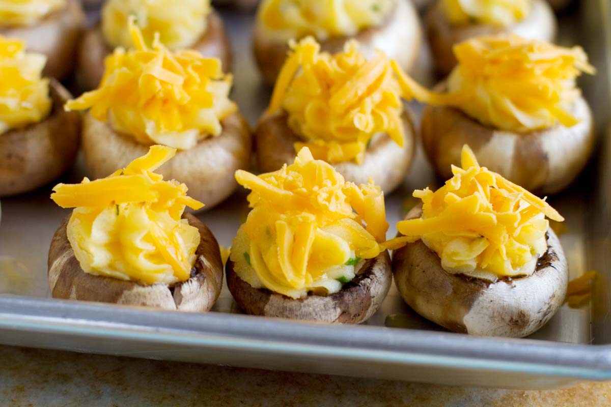 putting cheese on top of stuffed mushrooms