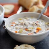 bowl of creamy chicken wild rice soup in a bowl with a spoon