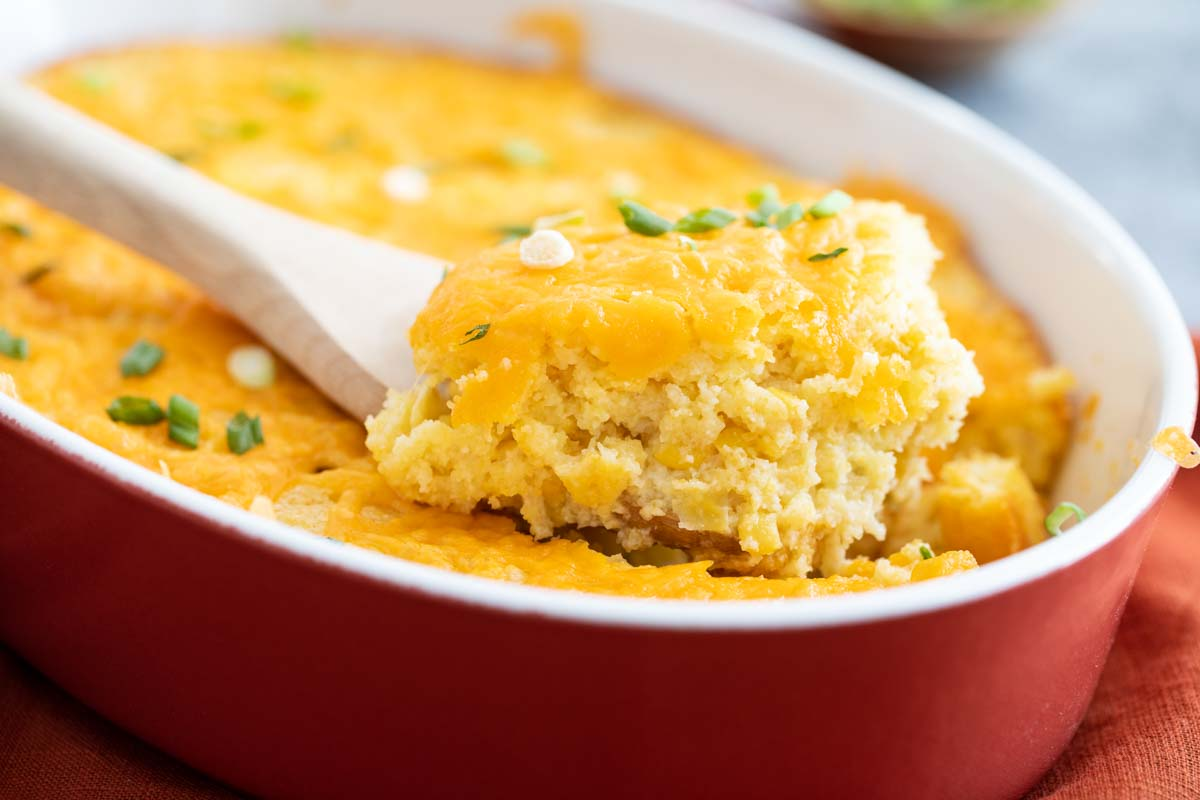 casserole dish with corn casserole with a spoon scooping the casserole out