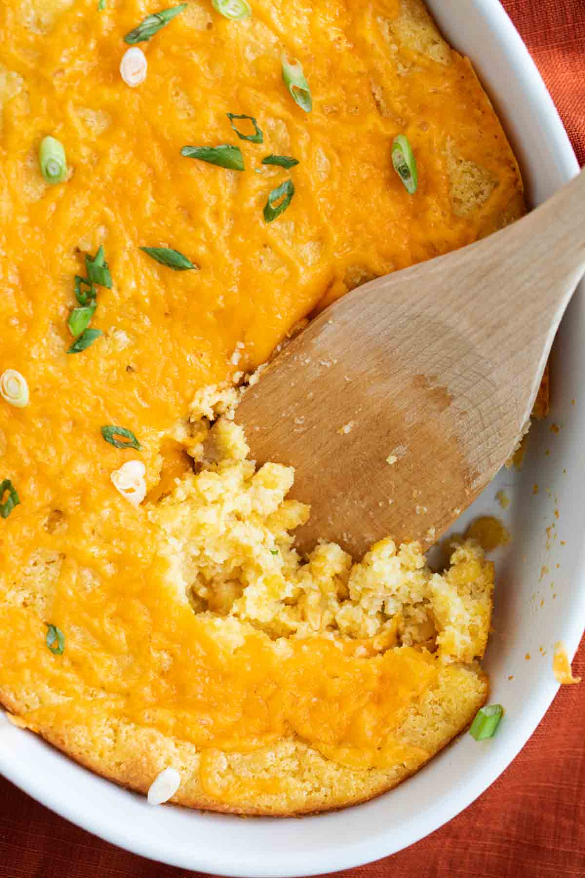 overhead view of corn casserole in a dish with a wooden spoon
