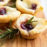 Cranberry Brie Bites with rosemary on a cutting board
