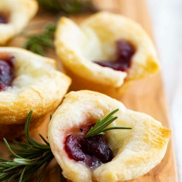 multiple cranberry brie bites on a cutting board