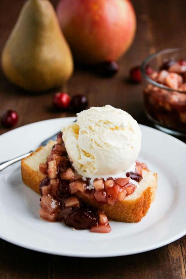 Cranberry Sauce over Pound Cake on a white plate with vanilla ice cream