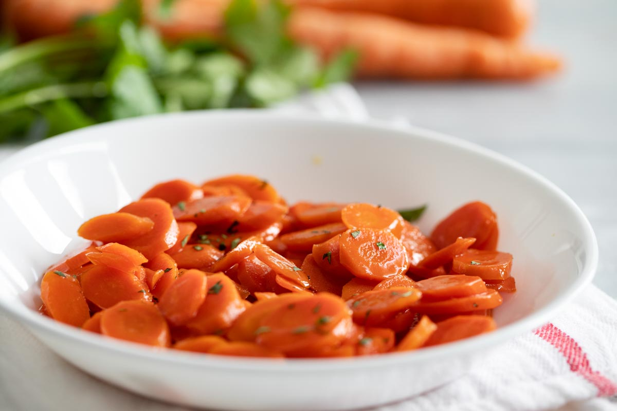 bowl with glazed carrots with parsley sprinkled on top