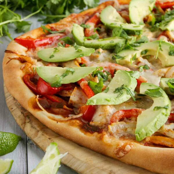 pizza topped with turkey, peppers, avocados and cheese
