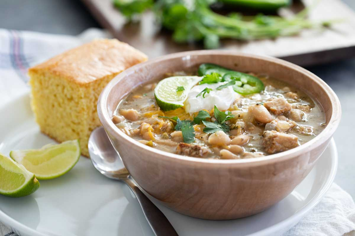 bowl of white turkey chili with cornbread and lime slices