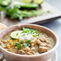 bowl of white turkey chili with beans topped with sour cream and jalapeno