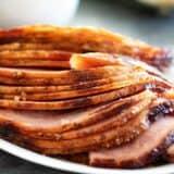 sliced brown sugar glazed ham on a plate