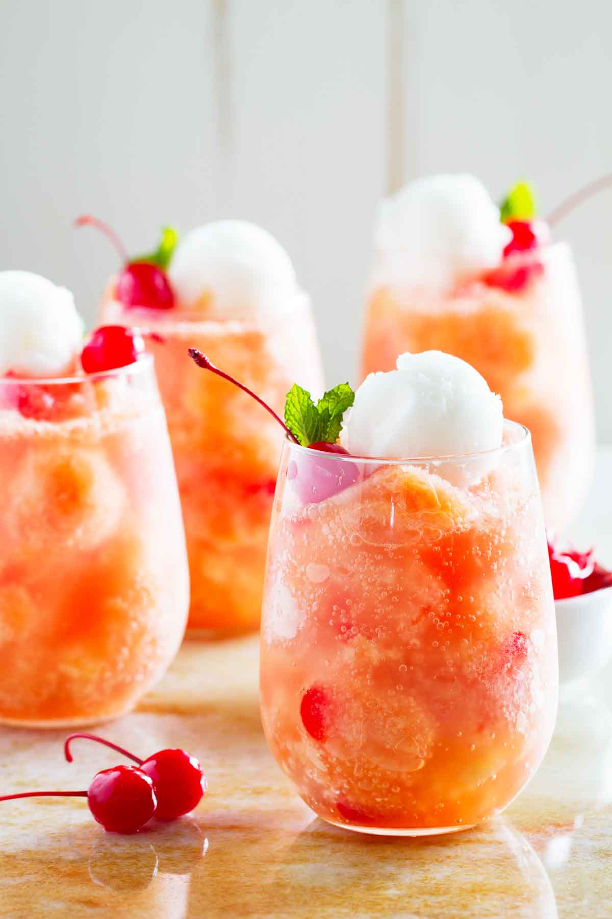 glasses of fruit freeze punch topped with sorbet and cherries