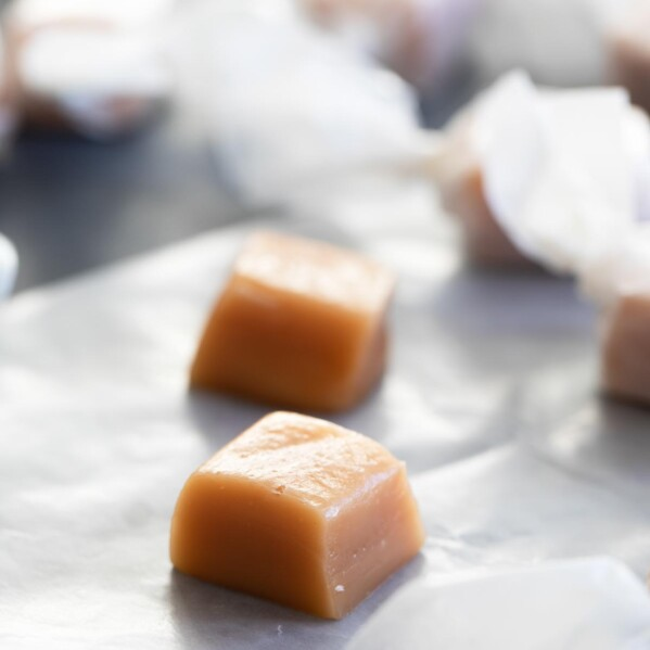 homemade caramel candy on a piece of waxed paper with more candy in the background