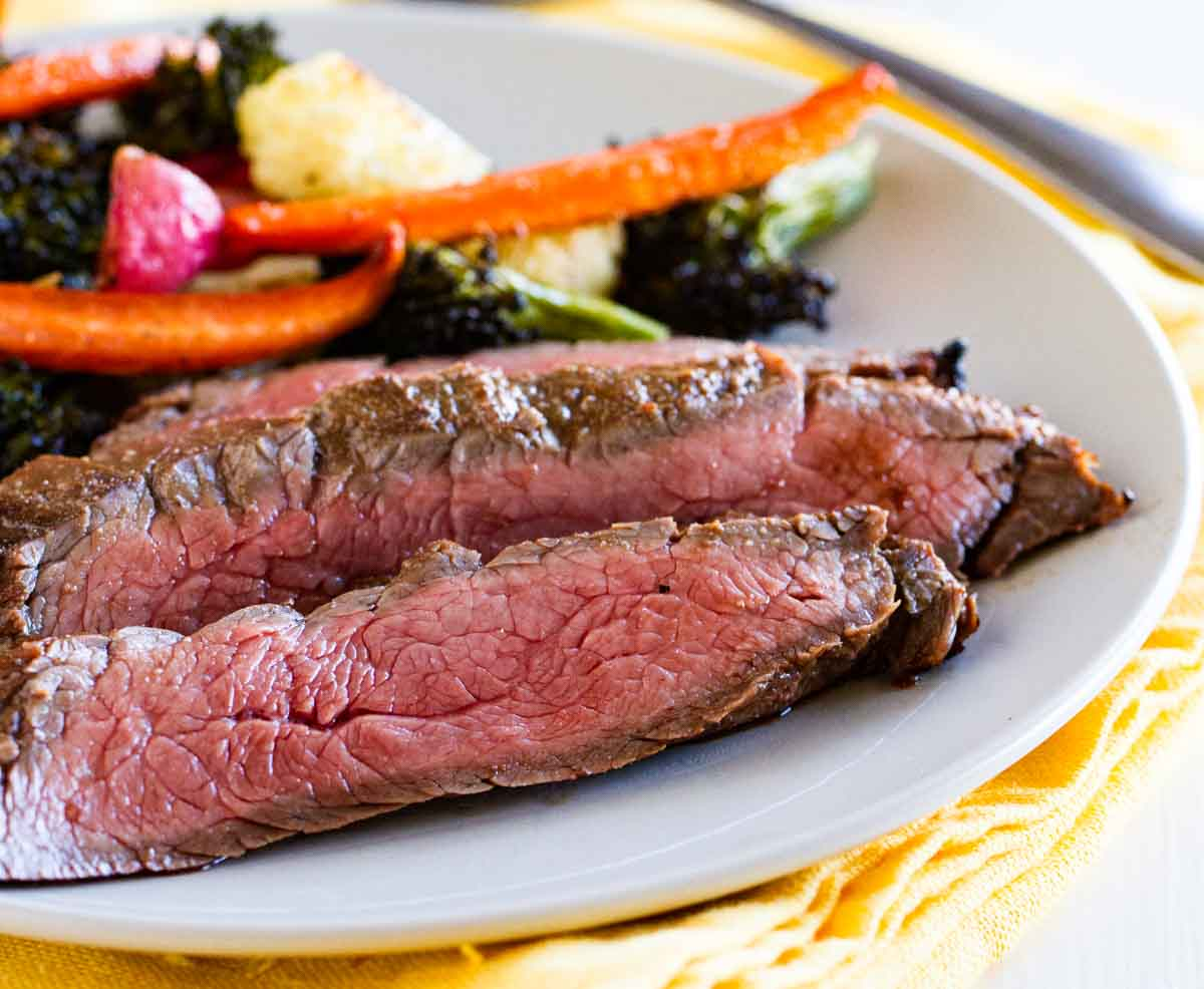 sliced grilled flank steak on a plate with vegetables