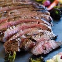 full sliced flank steak on a baking sheet