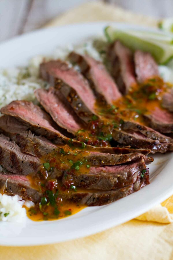 sliced flank steak with chipotle butter over rice on a platter