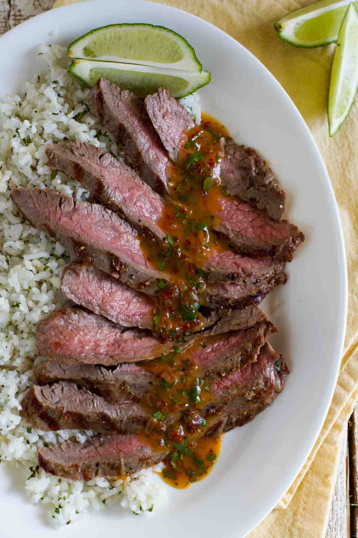 overhead view of sliced flank steak with chipotle butter