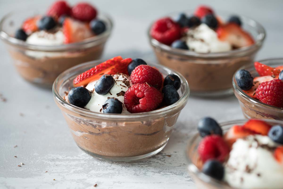 bowls of chocolate mousse topped with berries and whipped cream