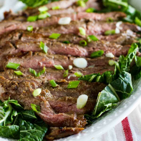 Korean Barbecue Flank Steak on a plate with greens