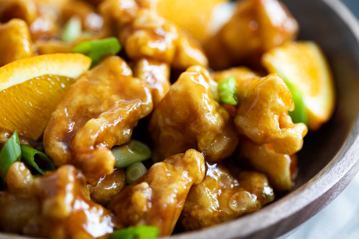 close up of orange chicken with pieces of orange and green onion