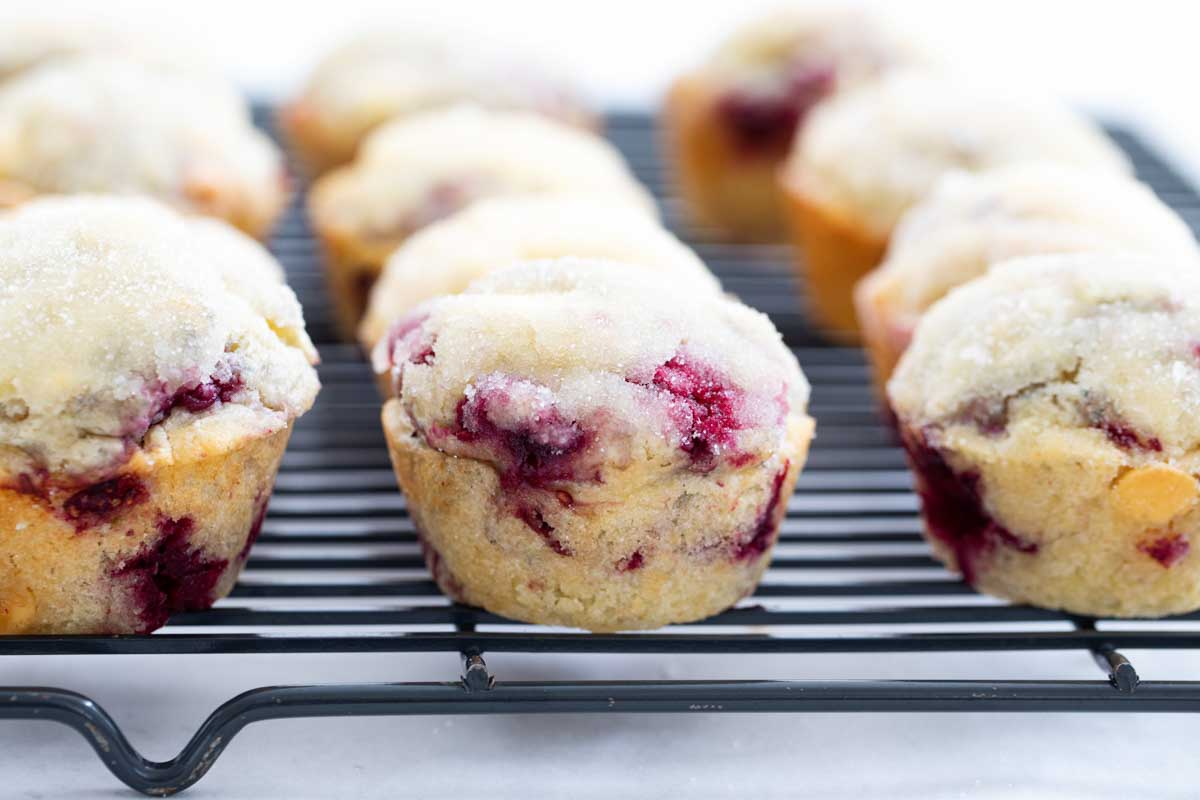 raspberry muffins with white chocolate chips on a cooling rack