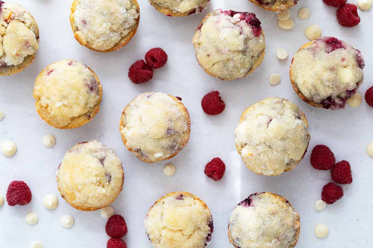 overhead view of muffins with raspberries and white chocolate chips