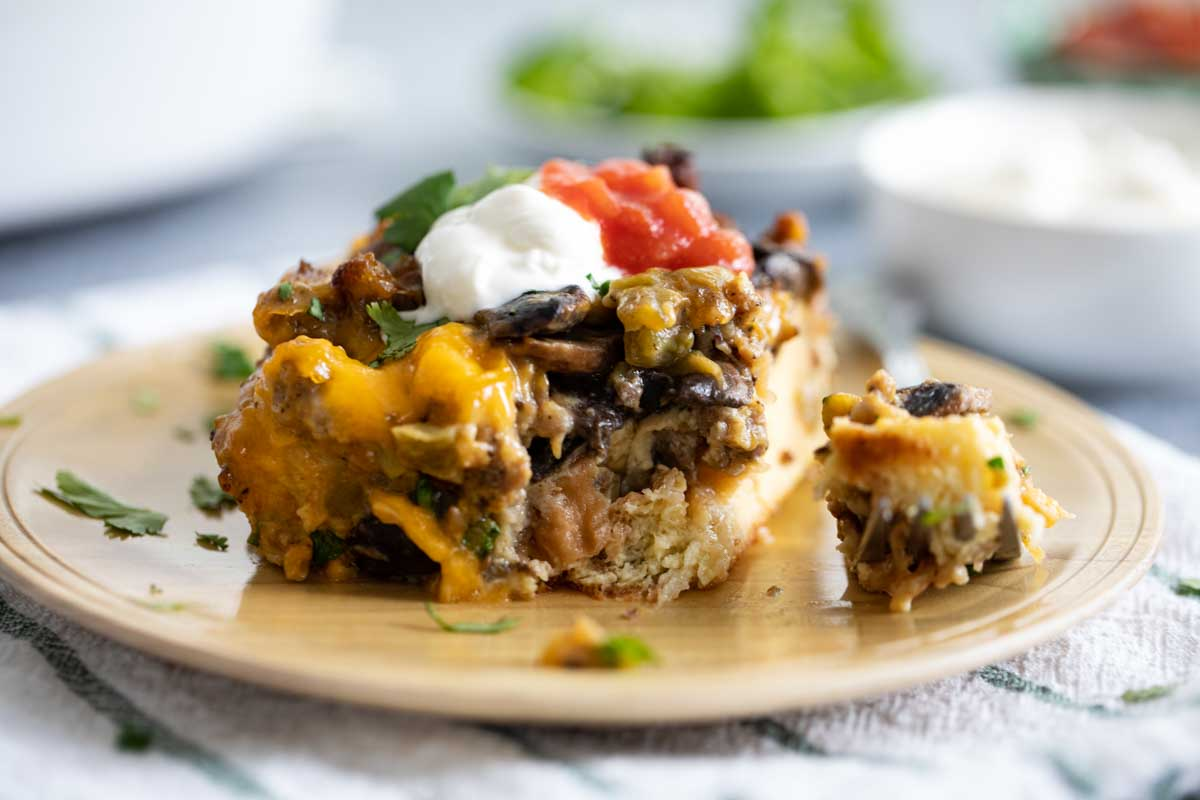 slice of sausage breakfast casserole with a forkful taken