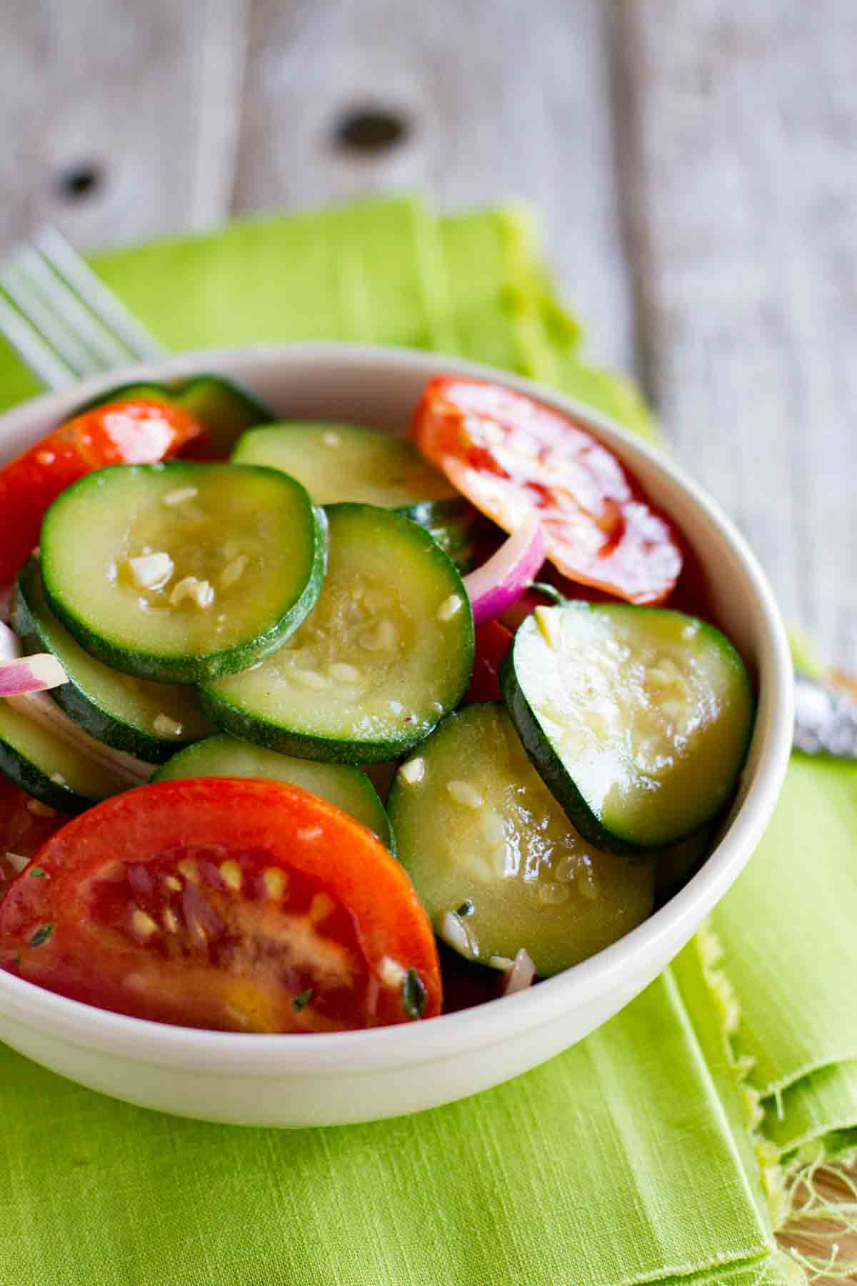 bowl of zucchini salad with tomatoes and red onions