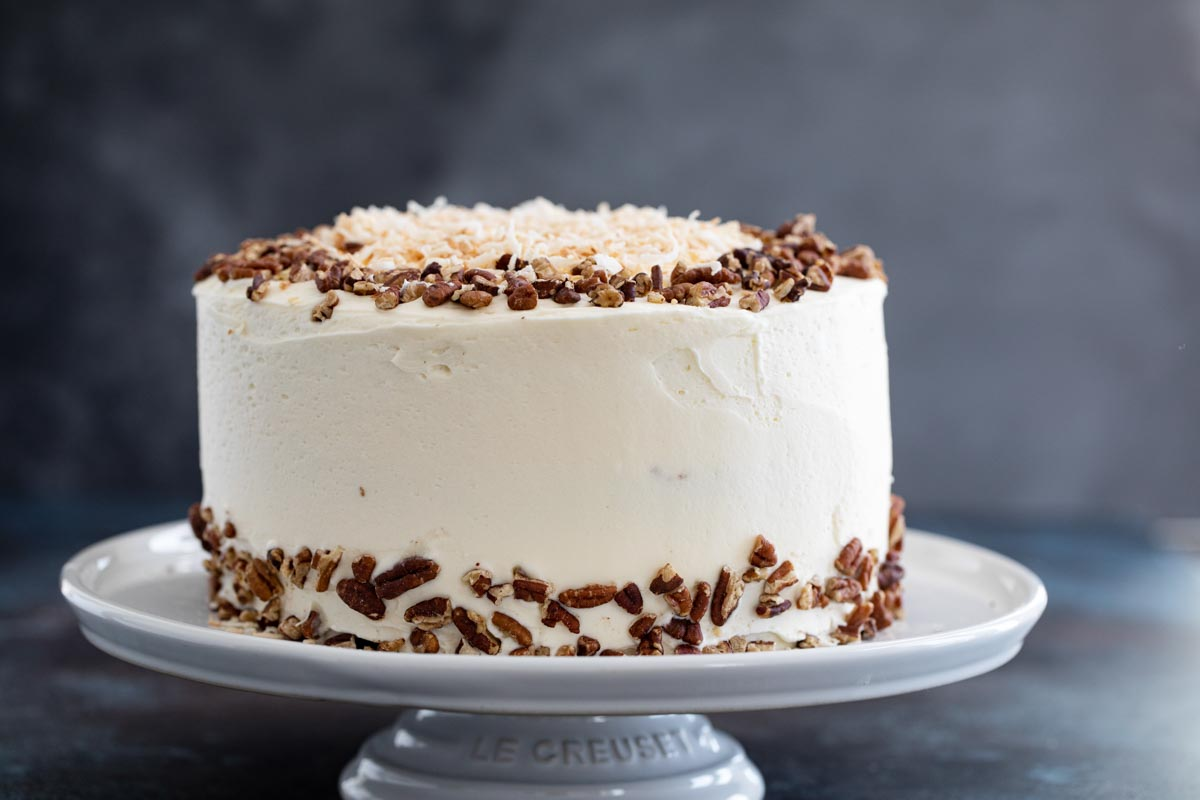 whole carrot cake decorated with pecans and coconut
