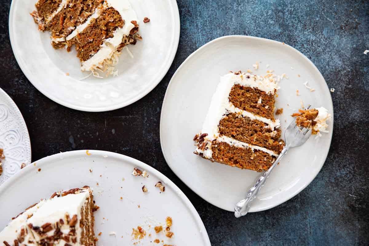 overhead view of plates of carrot cake with frosting