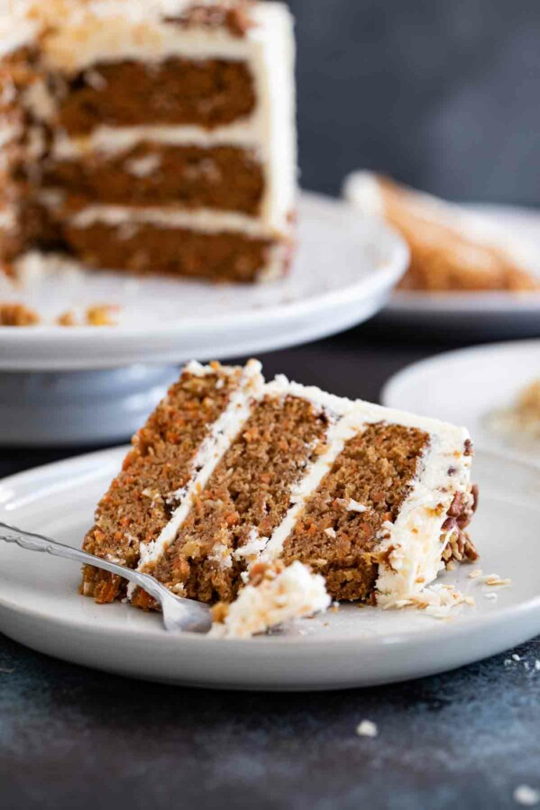slice of carrot cake with a full carrot cake behind