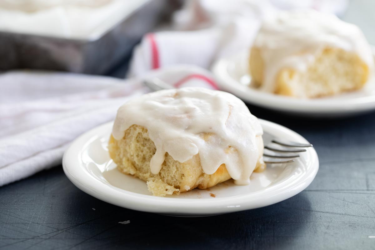Cinnamon roll with icing on a white plate
