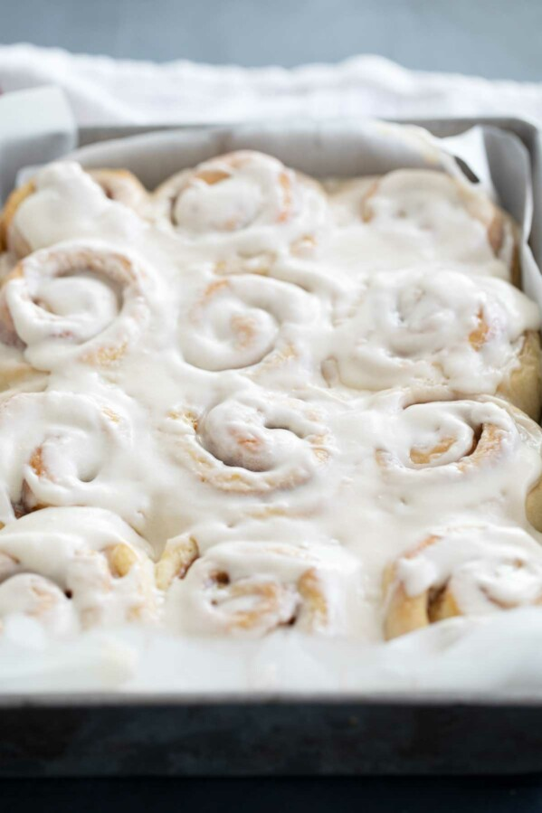 pan full of cinnamon rolls with icing