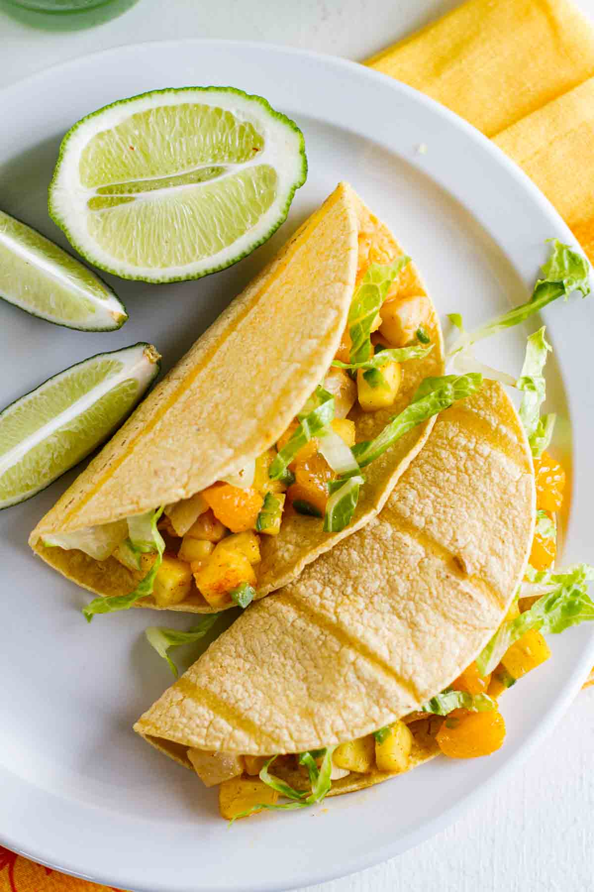 overhead view of citrus fish tacos with fruit salsa with limes on the plate