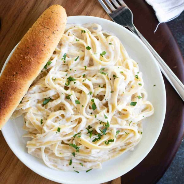 overhead view of Easy Alfredo Sauce and pasta on a plate with a breadstick