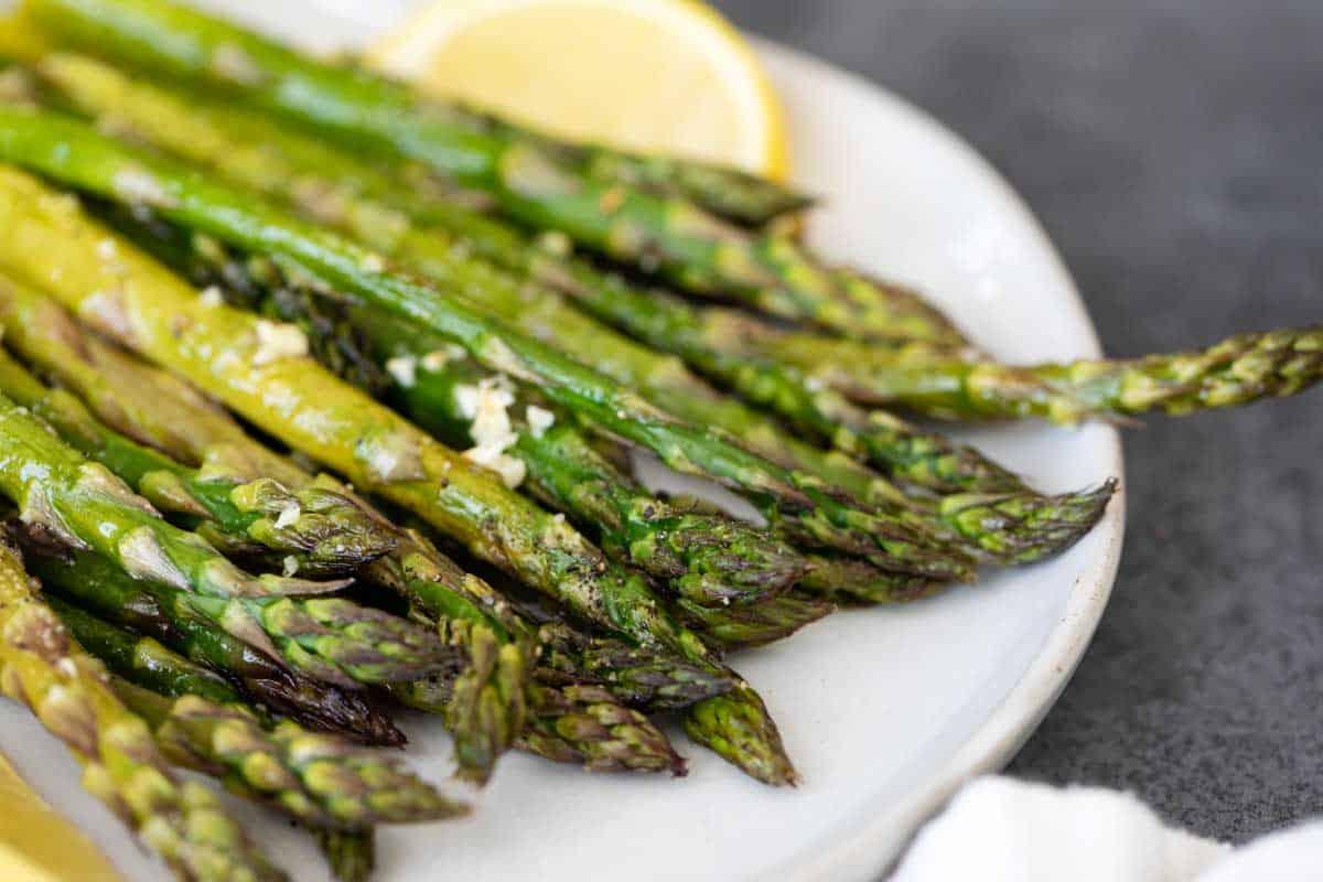 roasted asparagus on a plate with lemon slice