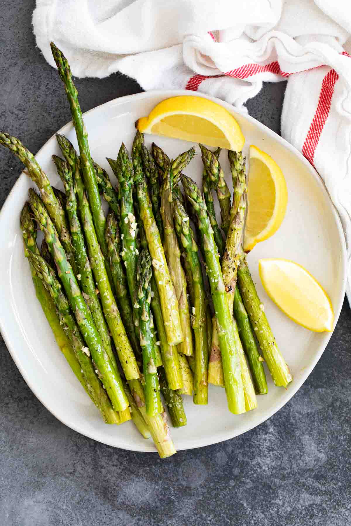 overhead view of roasted asparagus on a white plate