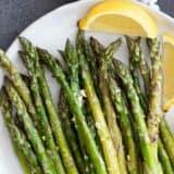 roasted asparagus on a plate with lemon slices