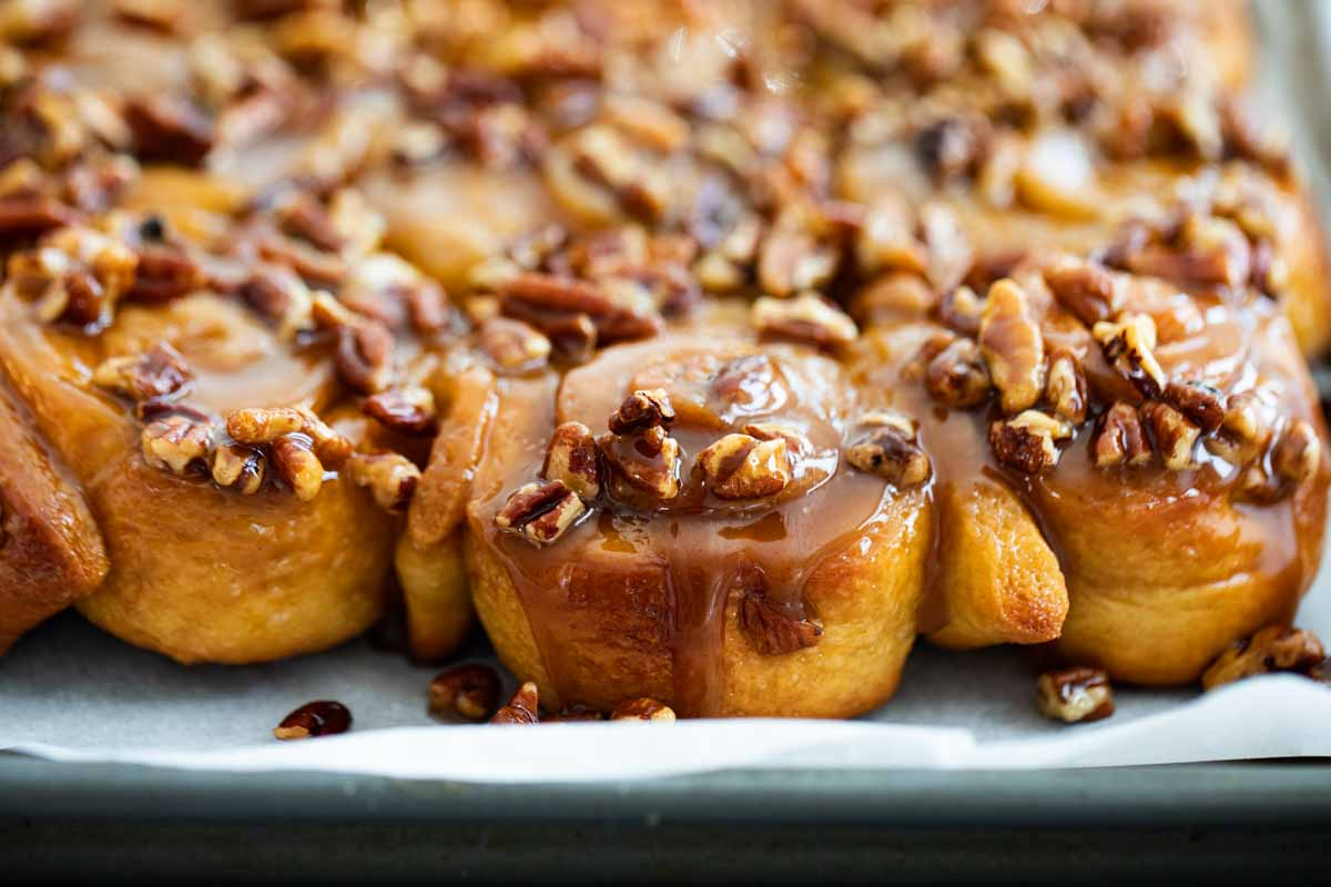caramel sticky buns on a tray topped with pecans