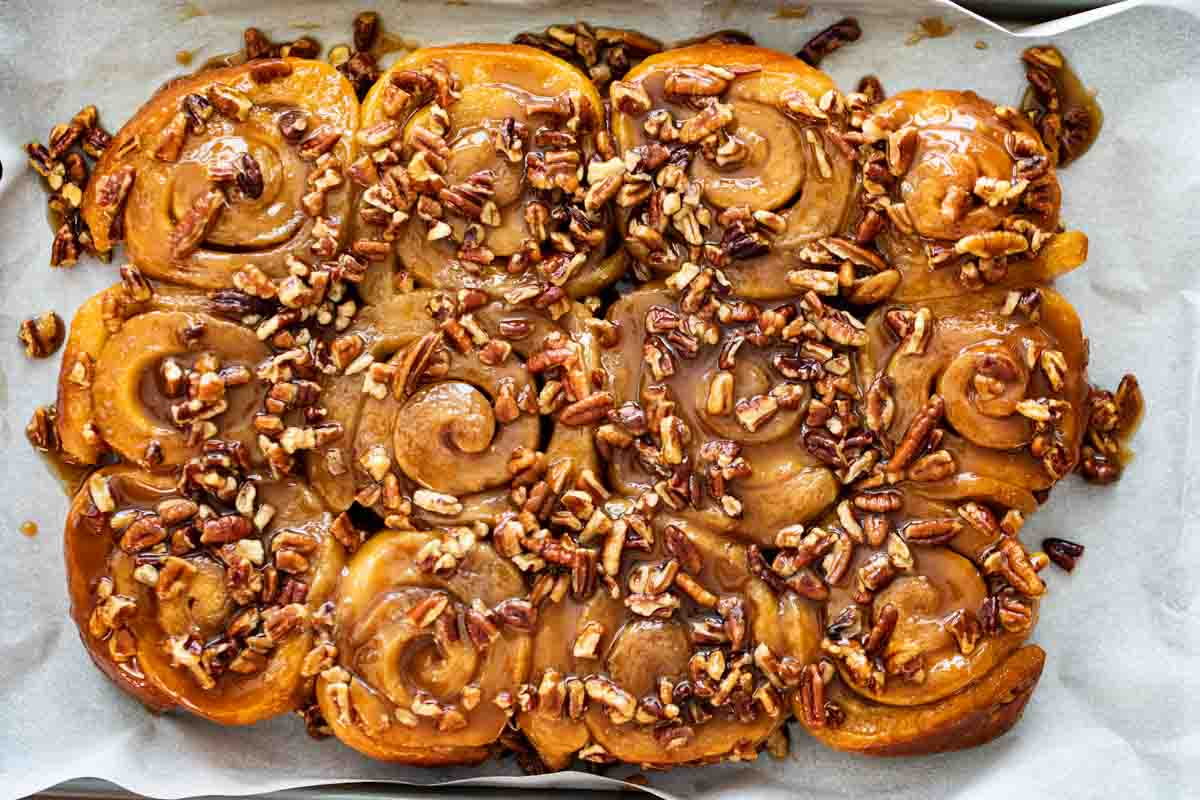 sticky buns that have been turned out from the pan onto a piece of parchment paper