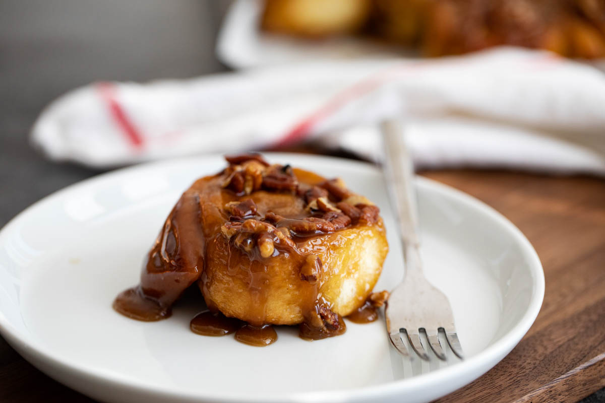 single sticky bun on a plate with a fork