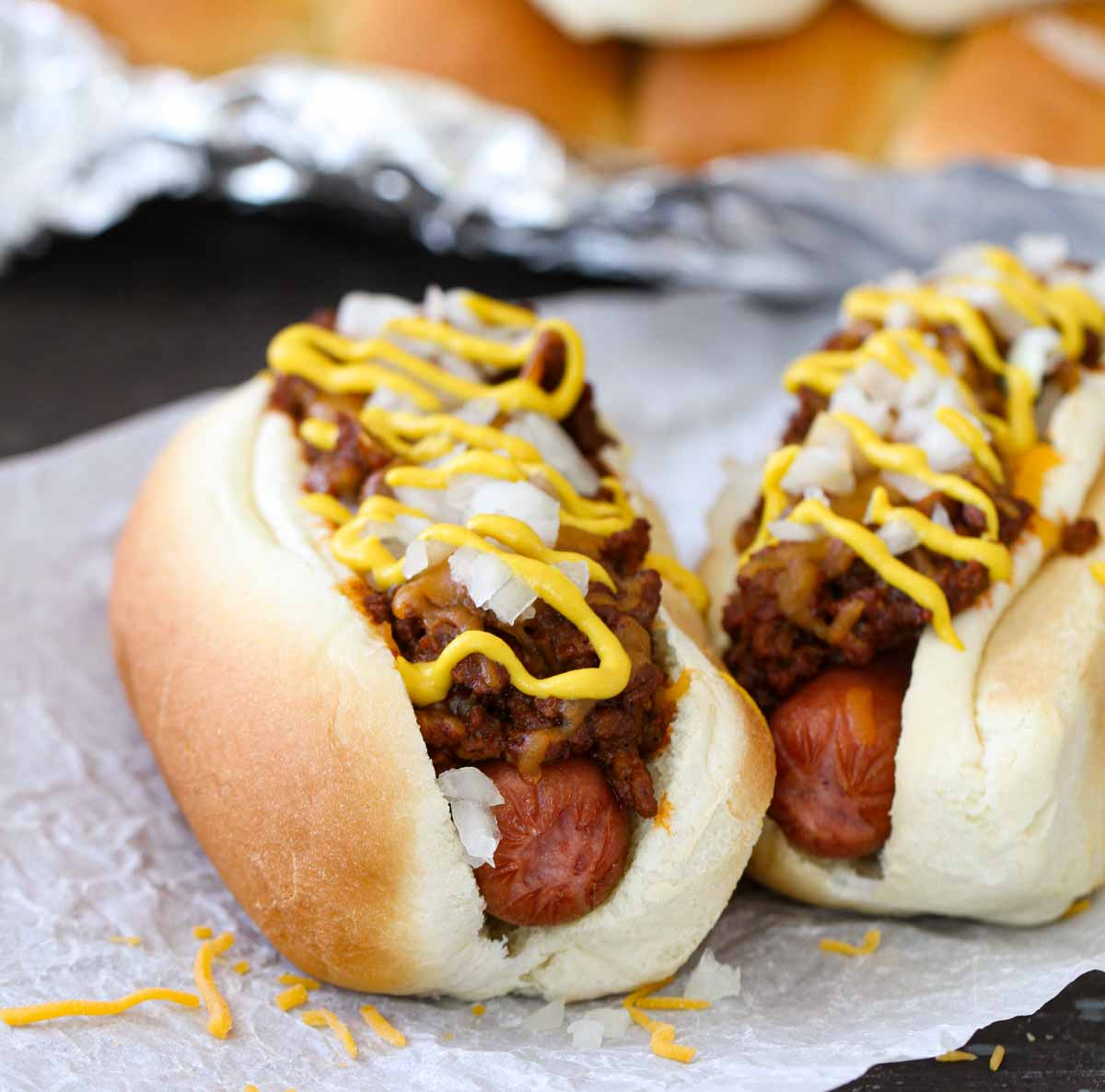 2 Coney Island Hot Dogs topped with mustard, cheese and onions