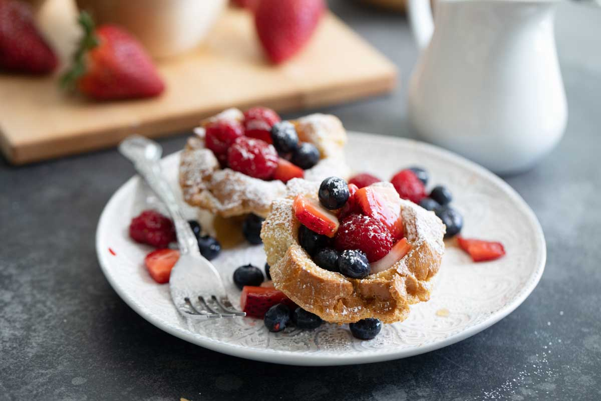 two french toast cups on a plate with fresh berries and powdered sugar