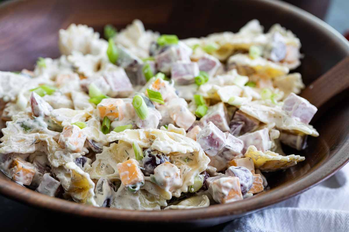 wooden bowl filled with bow tie pasta salad with creamy dressing
