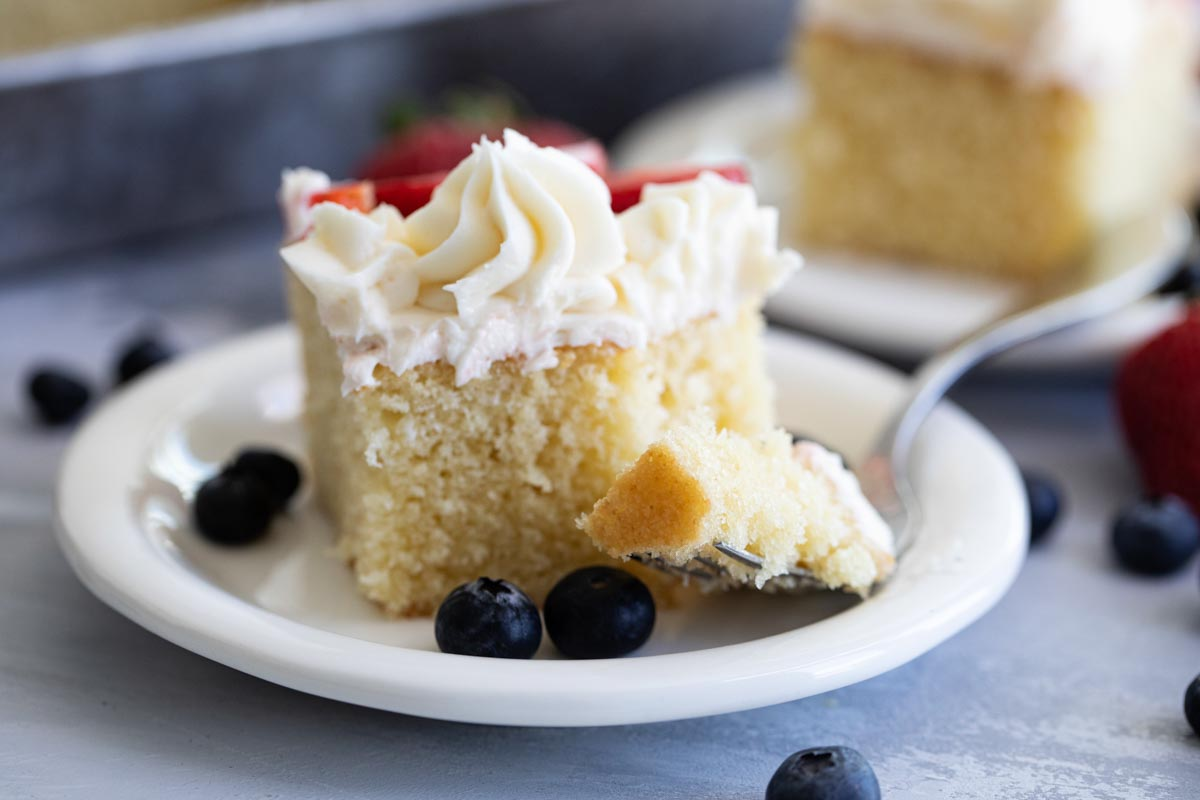 fork in white cake with buttercream and fruit
