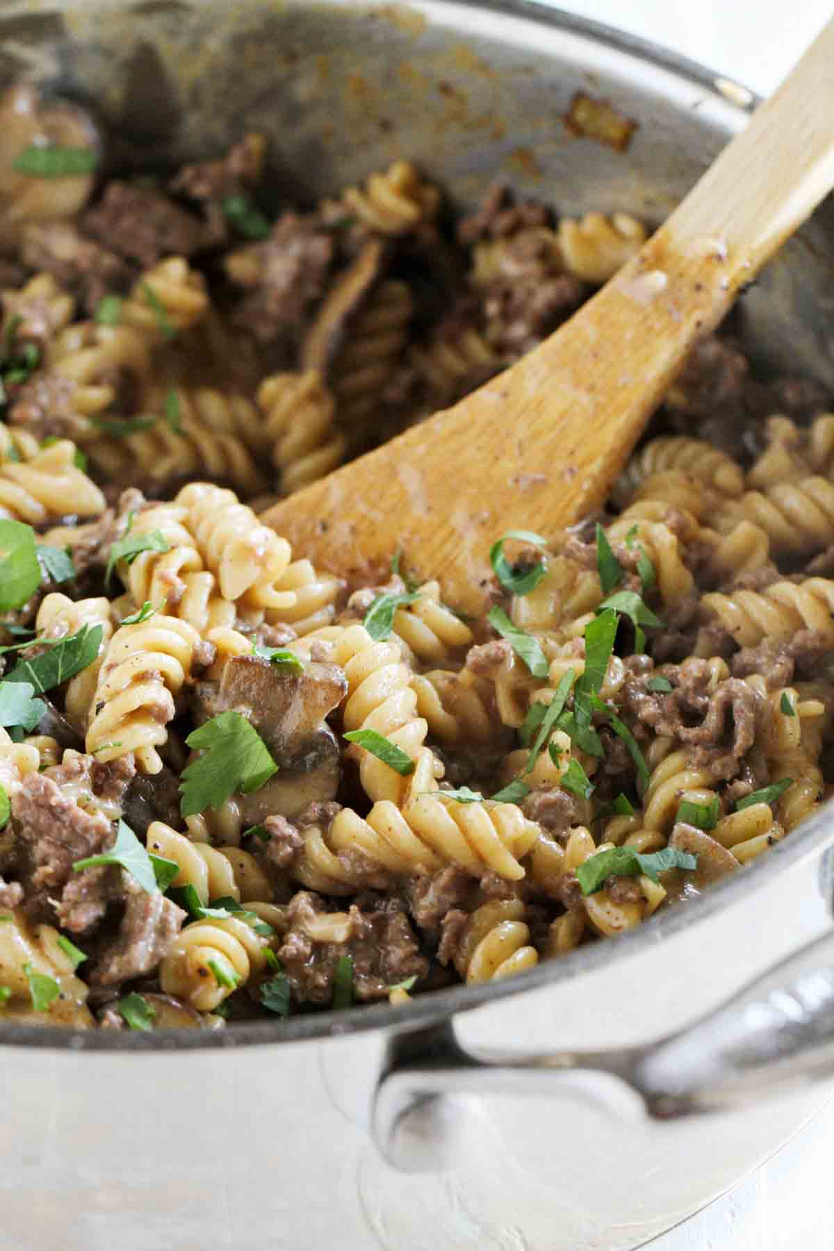 pot with ground beef stroganoff and wooden spoon