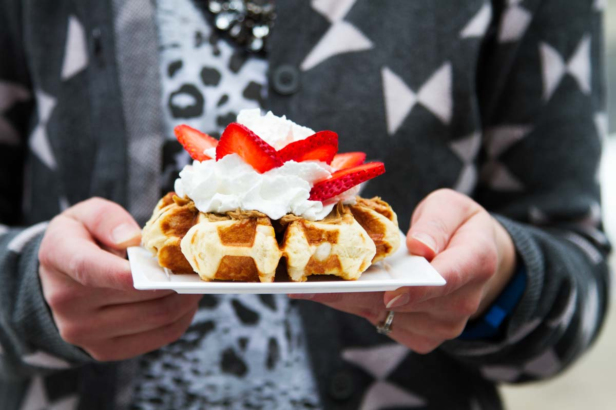 holding a plate with a liege waffle topped with whipped cream and strawberries