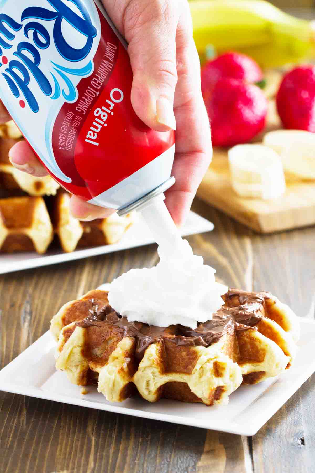 putting whipped topping on a liege waffle