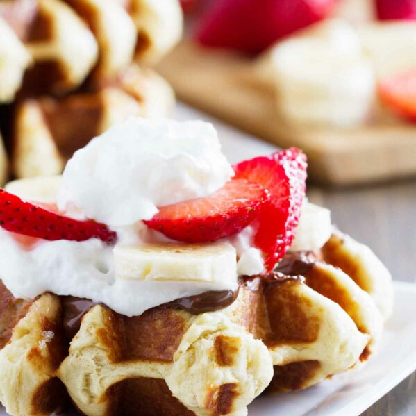 Liege waffle topped with nutella, bananas, strawberries and whipped cream