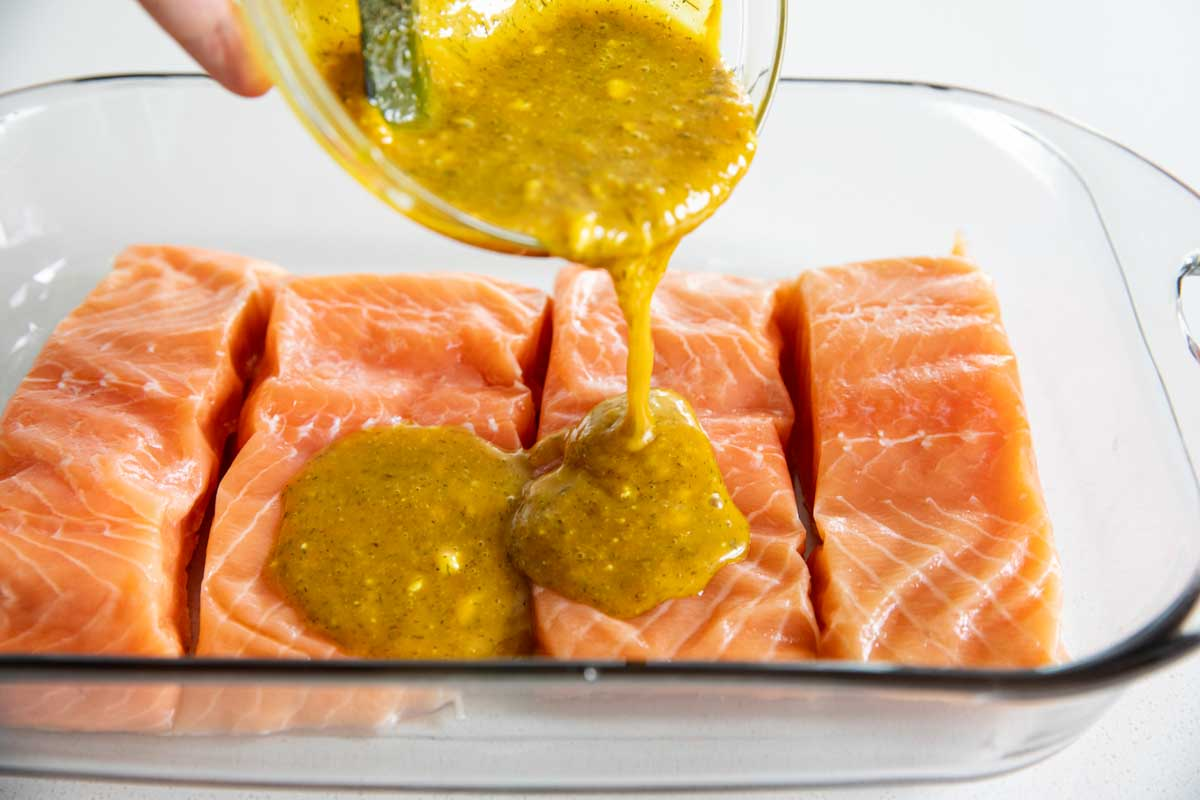 pouring honey mustard over salmon in a baking dish